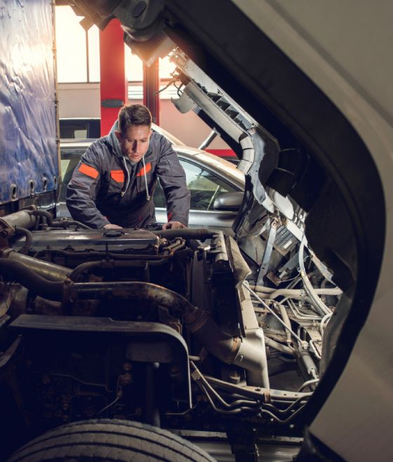 Man working under hood of commercial vehicle